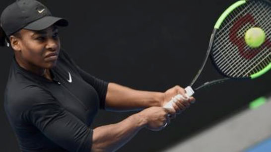 Serena Williams hitting tennis ball with racket